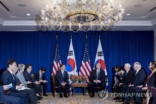 美国东部时间21日,在纽约,文在寅与特朗普在韩美首脑会谈前交谈。(韩联社/法新社)