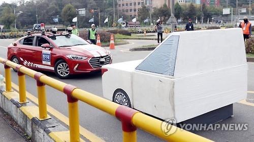 资料图片:自动驾驶汽车现场演示躲避障碍物(韩联社)