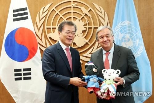 当地时间9月18日,在纽约联合国总部办公室,韩国总统文在寅(左)与联合国秘书长古特雷斯手持平昌冬奥会吉祥物合影留念。(韩联社)