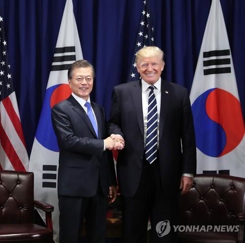 当地时间9月21日,在美国纽约乐天皇宫酒店,韩国总统文在寅(左)和美国总统特朗普亲切握手合影。(韩联社)