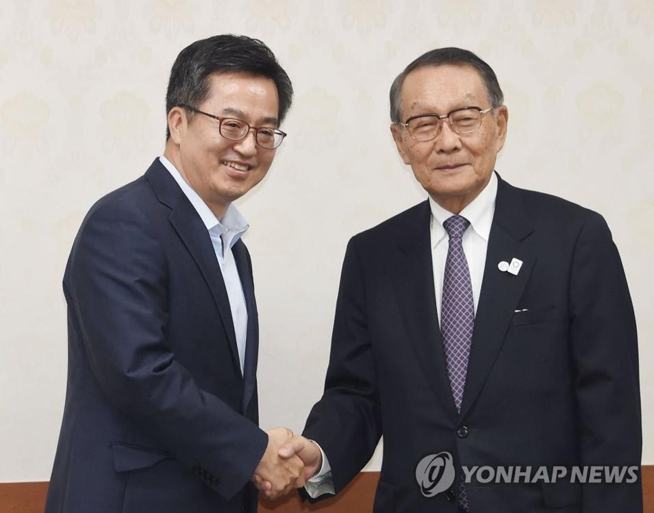 9月26日,在中央政府首尔办公大楼,韩国经济副总理兼企划财政部长官金东兖(左)与日韩经济协会会长佐佐木干夫握手。(韩联社/企划财政部提供)