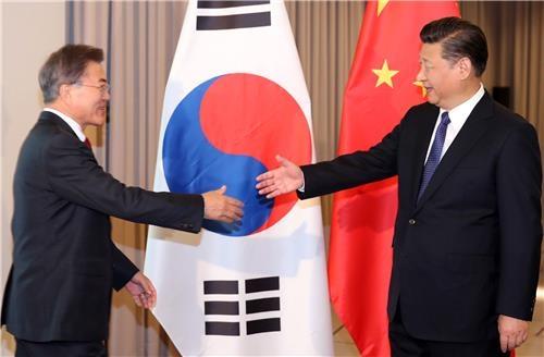 资料图片:韩中元首握手。(韩联社)
