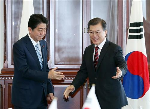 资料图片:韩日首脑寒暄。(韩联社)