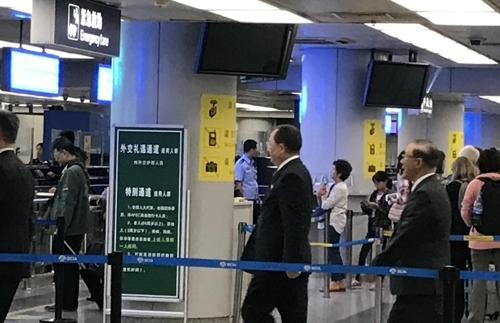 9月28日,在首都机场,李勇浩(右二)走入外交礼遇通道。(韩联社)