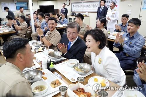 文在寅与夫人金正淑女士同官兵们共进午餐,亲切交谈。(韩联社)