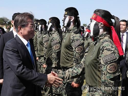 文在寅与一名女特工队员握手。(韩联社)