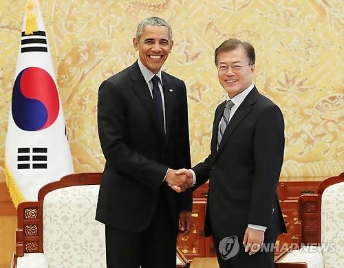 资料图片:韩国总统文在寅(右)与前美国总统奥巴马握手。(韩联社/青瓦台提供)