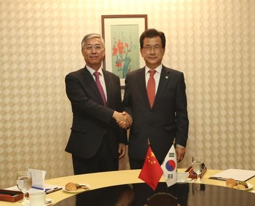 9月29日,在韩国清州第七届中国留学生节期间,中国驻韩大使邱国洪(左)与忠清北道知事李始钟举行会晤并握手合影。(韩联社)