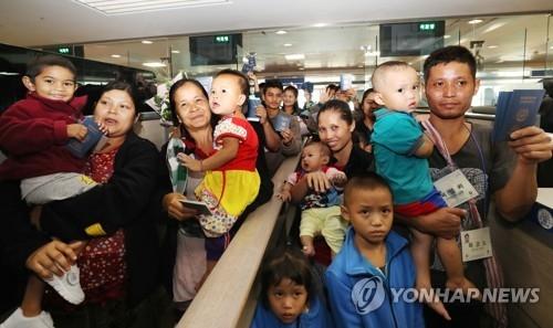 资料图片:7月25日上午,在仁川机场,4户缅甸家庭的23名难民通过边检入境韩国。(韩联社)