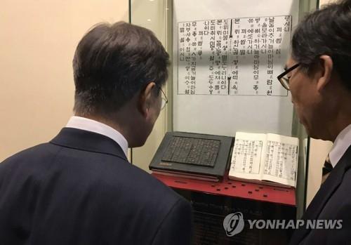 资料图片:文在寅(左)在出席联大期间参观陈列于联合国总部的《月印千江之曲》。(韩联社/青瓦台提供)