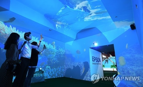 资料图片:2017清州工艺双年展上,参观游客在馆内拍照留念。(韩联社)