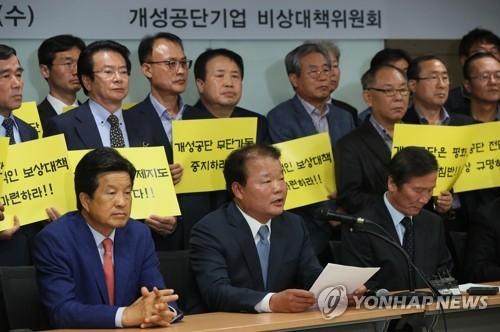 10月11日,在首尔市,开城韩商们正式表态坚决反对朝方擅自开工,开城园区企业协会会长申汉龙(前排居中)正在答记者问。(韩联社)