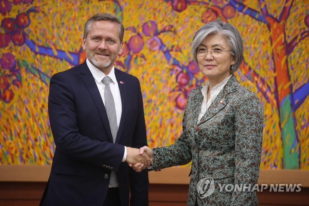 10月13日,在首尔韩国外交部大楼,韩国外长康京和(右)同丹麦外交大臣萨穆埃尔森握手合影。(韩联社)