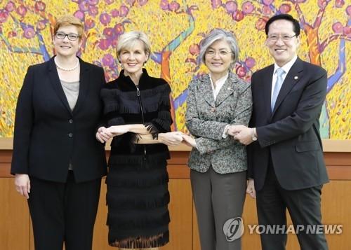10月13日上午,在首尔韩国外交部,佩恩(左起)、毕晓普、康京和、宋永武在韩澳外长防长会前牵手合影。(韩联社)
