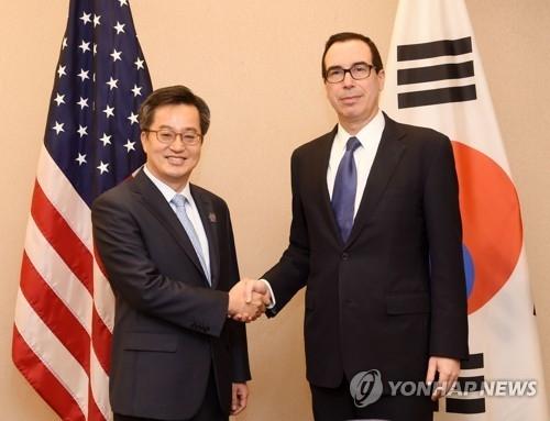 当地时间10月14日,在美国华盛顿,韩国经济副总理兼企划财政部长官金东渊(左)与美国财长姆努钦举行会谈前握手。(韩联社/企划财政部提供)