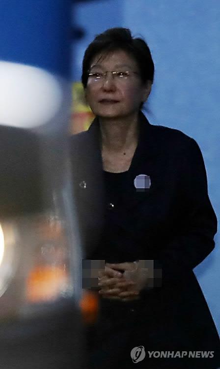 10月16日上午,在首尔中央地方法院,朴槿惠在延长羁押后首次庭审后走出法庭。(韩联社)