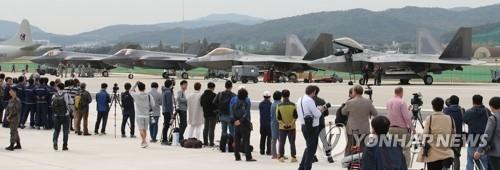 停在首尔机场的F-22和F-35A引来众人围观。(韩联社)