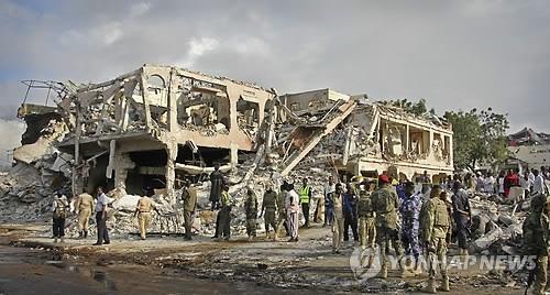 10月14日下午(当地时间),东非索马里首都摩加迪沙发生历史上最严重的炸弹恐怖袭击,造成数百人伤亡。图为15日索马里首都摩加迪沙恐怖袭击事件现场,军警在废墟堆里搜寻伤者和牺牲者遗体。(韩联社/美联社)