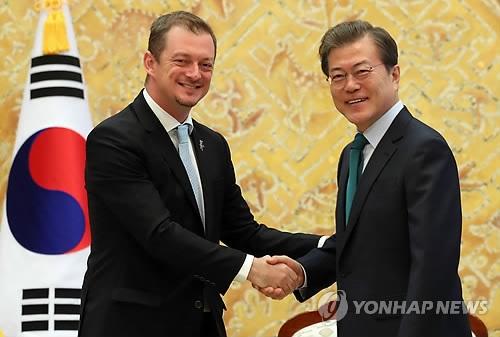 10月17日下午,在韩国总统府青瓦台,韩国总统文在寅与国际残奥委会(IPC)主席安德鲁·帕森斯握手。(韩联社)