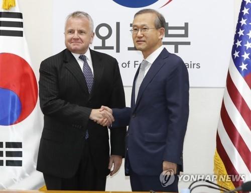 10月18日上午,在韩国外交部,林圣男(右)和沙利文在进行副外长战略对话前握手合影。(韩联社)