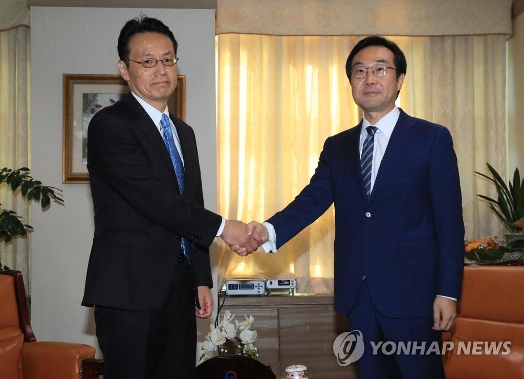 10月19日,在首尔韩国外交部大楼,朝核六方会谈韩方团长李度勋(右)和日方团长金杉宪治握手合影。(韩联社)