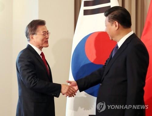 资料图片:当地时间7月6日,在柏林,文在寅(左)和习近平在韩中首脑会谈上亲切握手。(韩联社)