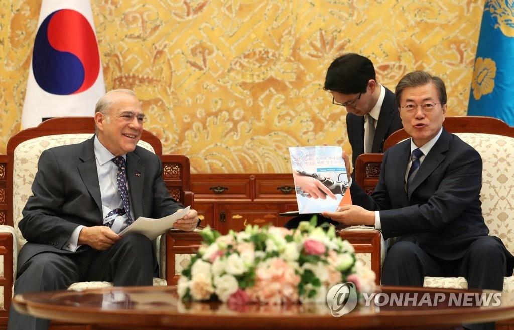 10月19日,在韩国总统府青瓦台,总统文在寅与经合组织秘书长安赫尔·古里亚交谈。(韩联社)