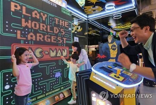 资料图片:一对父女在玩游戏机。(韩联社)