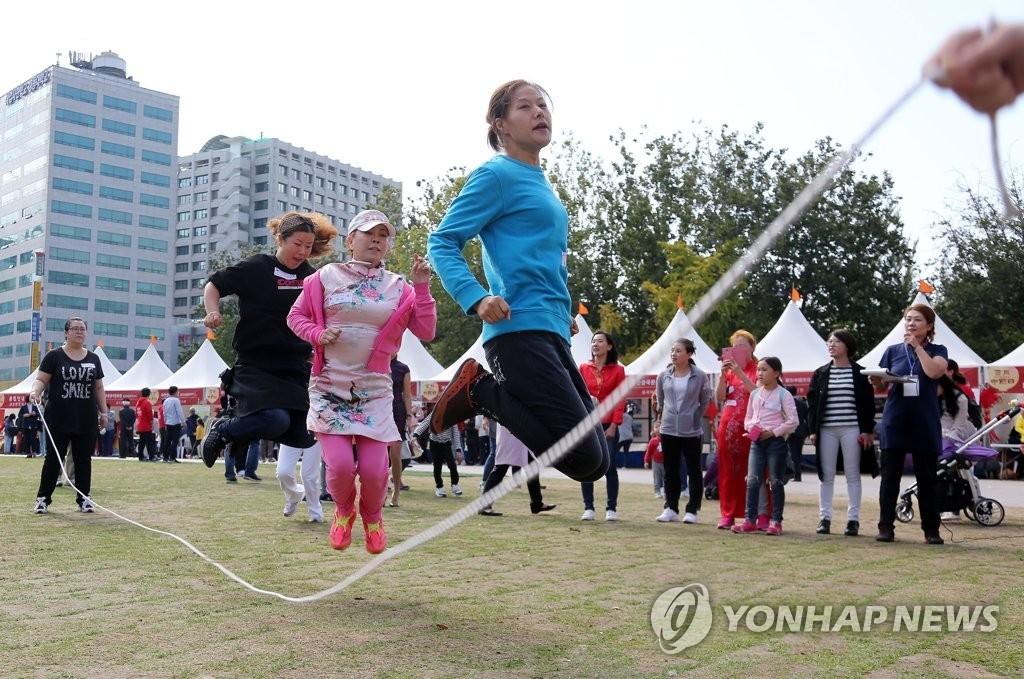 """10月22日,在首尔广场,市民们在""""首尔·中国日""""活动上齐跳绳共享欢乐。(韩联社)"""