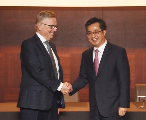 10月23日,在首尔新罗酒店,经济副总理兼企划财政部长官金东渊(右)同绿色气候基金(GCF)秘书处执行主任霍华德·拜姆森(Howard Bamsey)举行会晤。图为双方在会谈前握手合影。(韩联社)