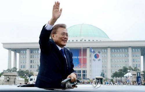 资料图片:5月10日,在首尔汝矣岛的国会,文在寅在第19届总统就职仪式结束后向民众挥手致意。(韩联社)