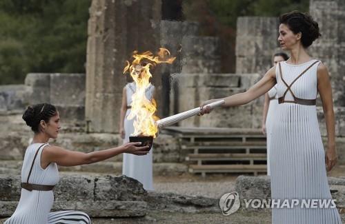 当地时间10月24日,扮演最高女祭司的希腊演员卡特里林娜·勒侯(右)点燃火种罐。(韩联社/美联社)