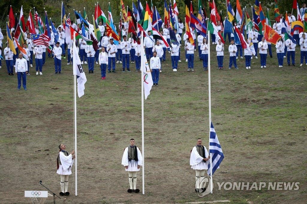 当地时间10月24日,在位于希腊伯罗奔尼撒半岛上的奥运会发源地古奥林匹亚,2018平昌冬奥会圣火采集成功。在现场奥林匹克圣歌的歌声中,奥林匹克会旗在圣火采集现场升起,后升起韩国和希腊国旗。(韩联社)