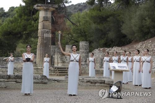 当地时间10月24日,扮演最高女祭司的希腊演员卡特里林娜·勒侯(中)高举火炬。(韩联社/美联社)