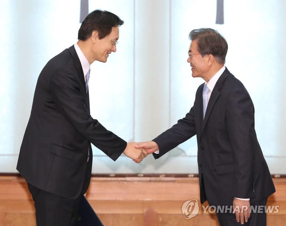 10月25日上午,在韩国总统府青瓦台,文在寅(右)与李洙勋握手。(韩联社)