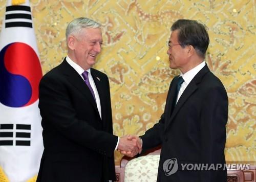 10月27日下午,在青瓦台,韩国总统文在寅与美国国防部长詹姆斯·马蒂斯握手致意。(韩联社)