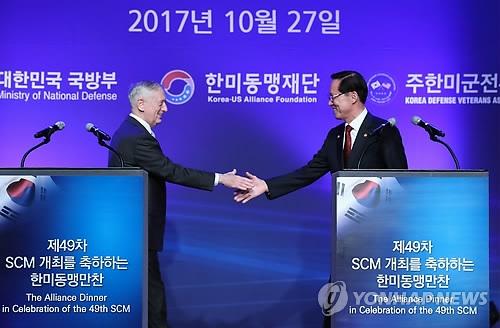 10月27日下午,在首尔,美国防长马蒂斯(左)和韩国防长宋永武出席由驻韩美军战友会和韩美同盟财团共同主办的韩美同盟晚宴。图为双方在致辞后握手。(韩联社)