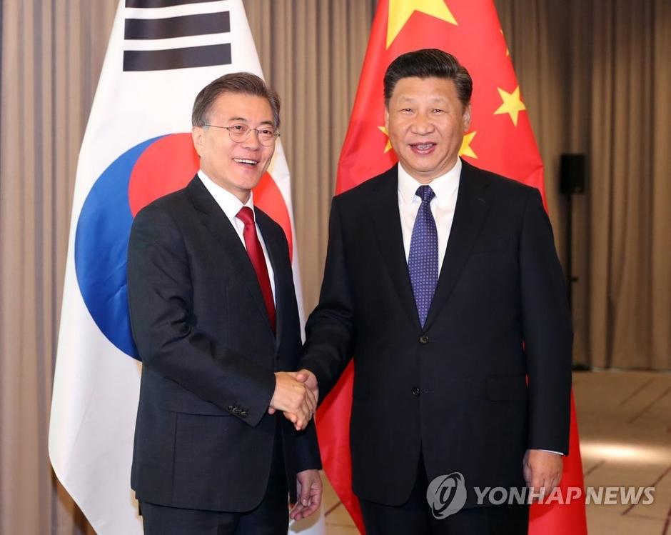 当地时间7月6日上午,在柏林,韩国总统文在寅(左)与中国国家主席习近平举行会谈并亲切握手。(韩联社)
