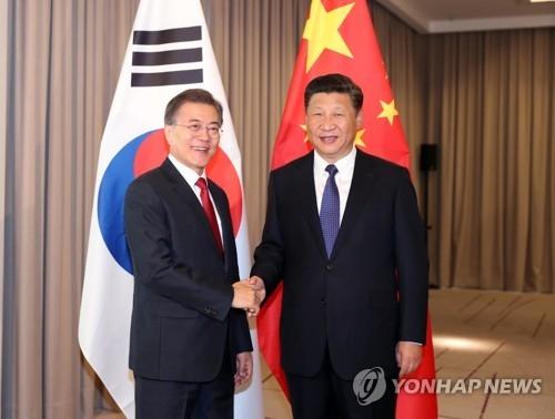 资料图片:当地时间7月6日,在德国柏林,韩国总统文在寅(左)与中国国家主席习近平握手合影。(韩联社)