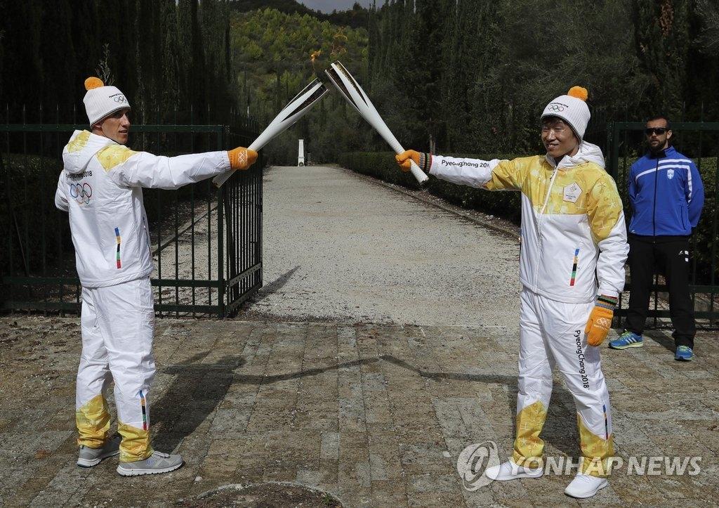 当地时间10月24日,韩国足球运动员朴智星(右)用平昌冬奥火炬接力第一棒火炬手、希腊越野滑雪运动员阿波斯托洛斯·阿格利斯手中的火炬引燃自己手中的火炬。(韩联社)