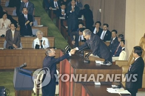 资料图片:1992年1月6日,老布什重回旧地,再次在韩国国会发表演讲。图为演讲结束后,老布什与时任国会议长朴浚圭握手。(韩联社/国会图书馆提供)