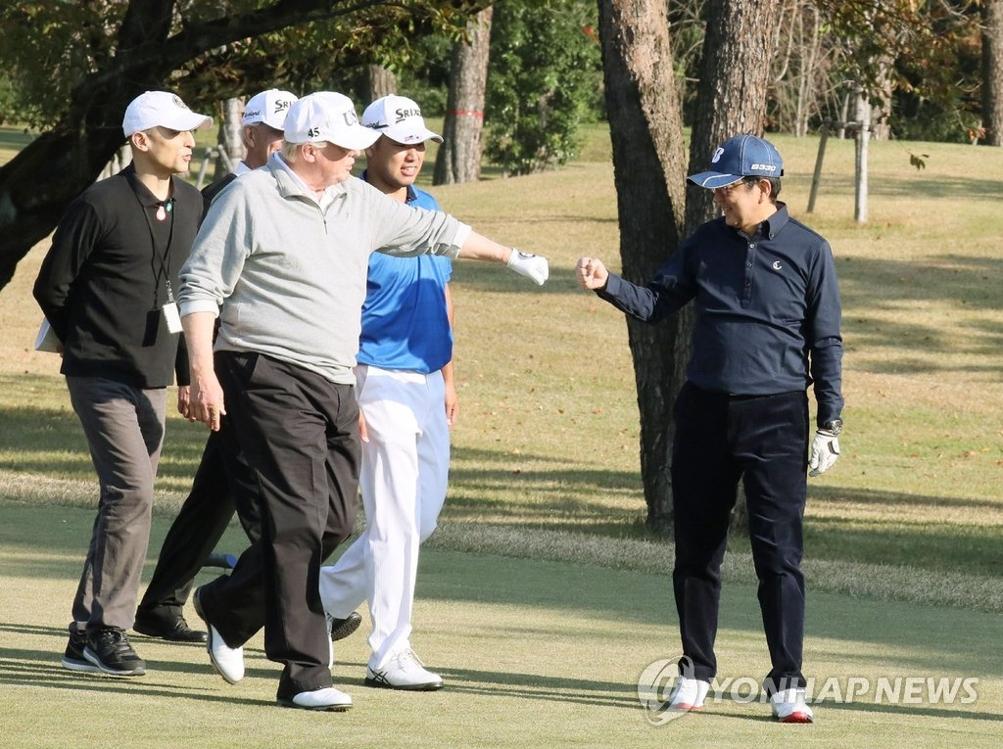 当地时间11月5日,在日本东京附近的埼玉县霞关乡村俱乐部球场,美国总统特朗普(右三)与日本首相安倍晋三(右一)在高尔夫球场上击拳示好。身着蓝色上衣的(中)是世界排名第四的日本高尔夫选手松山英树。(韩联社/法新社)
