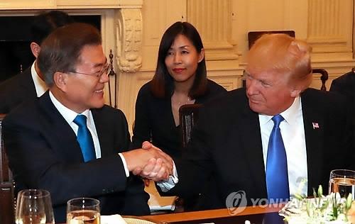 资料图片:当地时间6月30日,在美国白宫,访美的韩国总统文在寅(左)与美国总统特朗普握手。(韩联社)