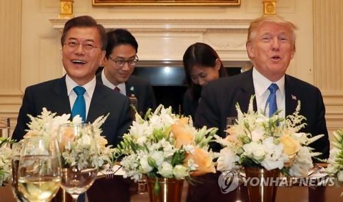 资料图片:当地时间6月29日,在白宫,文在寅(左)和特朗普在欢迎晚宴上相见欢。(韩联社)