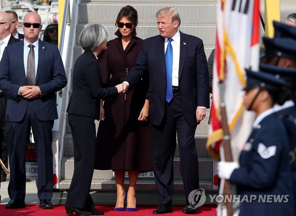 11月7日,在京畿道乌山美军基地,美国总统特朗普(右一)下机后与到机场迎接的韩国外交部长官康京和(右三)亲切握手。(韩联社)
