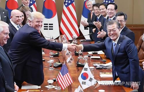 11月7日,在青瓦台,韩美两国总统在会谈前握手。(韩联社)