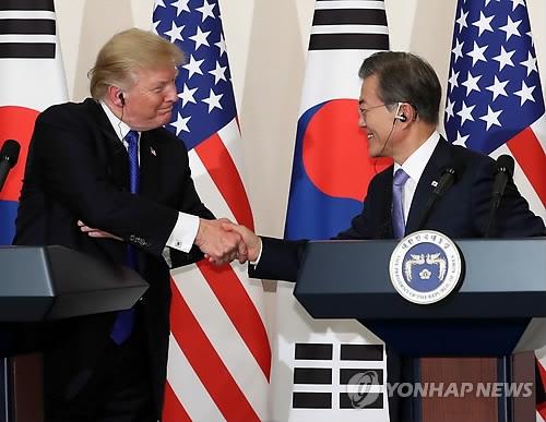 11月7日下午,在青瓦台,韩美两国总统在记者会上握手一笑。(韩联社)