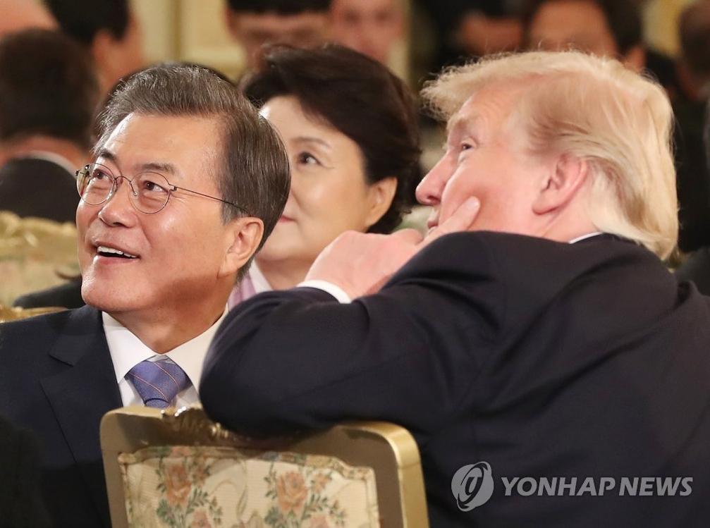 资料图片:11月7日,在青瓦台,韩国总统文在寅(左)与美国总统特朗普在国宾晚宴上共赏华盛顿之行的照片。(韩联社)