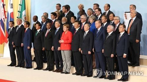 资料图片:当地时间7月7日,在德国汉堡,韩国总统文在寅(前排右一)、中国国家主席习近平(前排右五)、德国总理默克尔(前排右六)、美国总统特朗普(前排左二)等全球首脑级人士在二十国集团(G20)领导人峰会上合影。(韩联社)