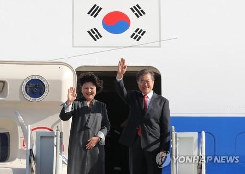 11月8日,在京畿道城南首尔机场,韩国总统文在寅(右)和夫人金正淑女士在进舱前向送行人群挥手致意。(韩联社)